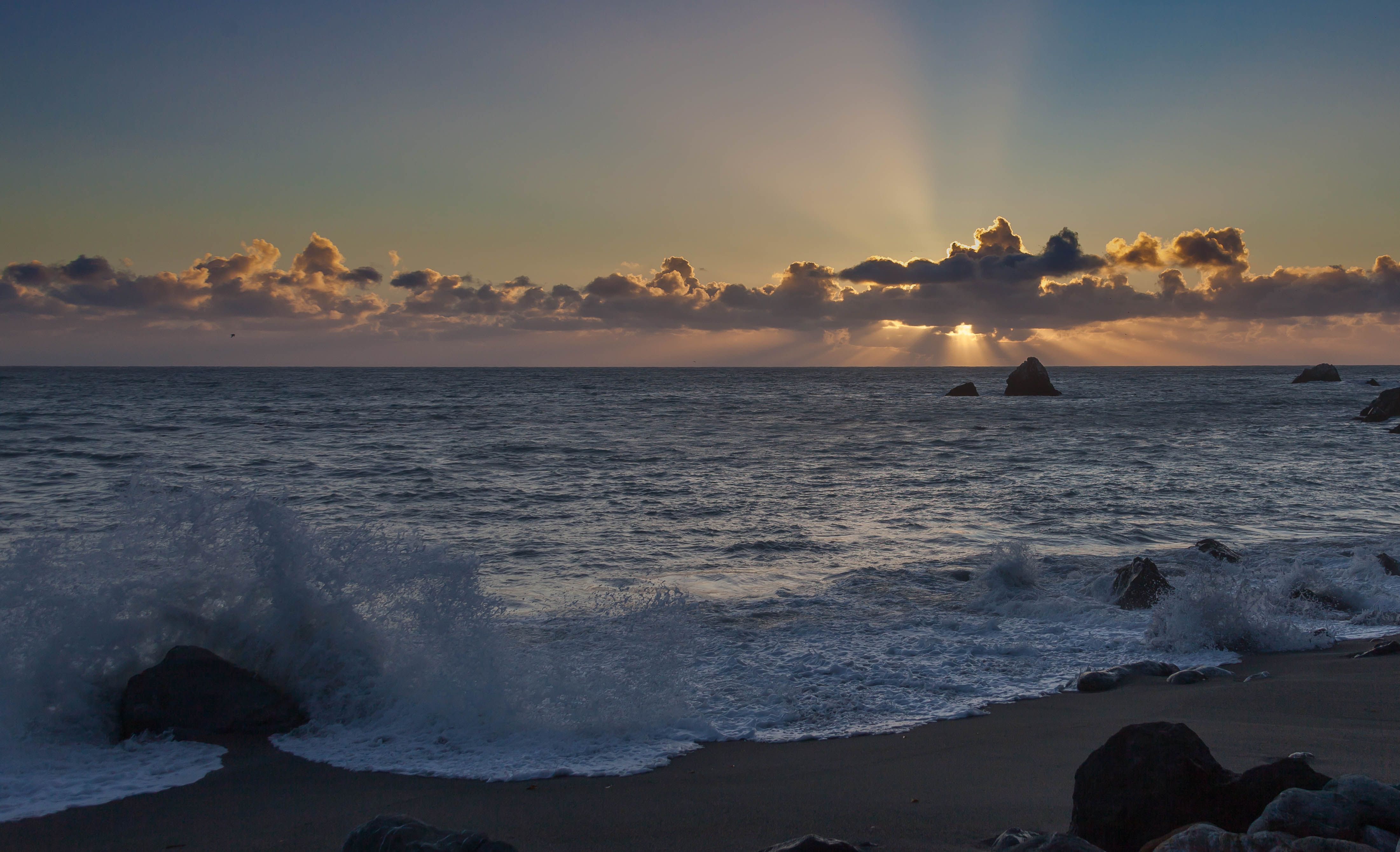 Sunset at Limekiln State Park, with a wave crashing on a rock