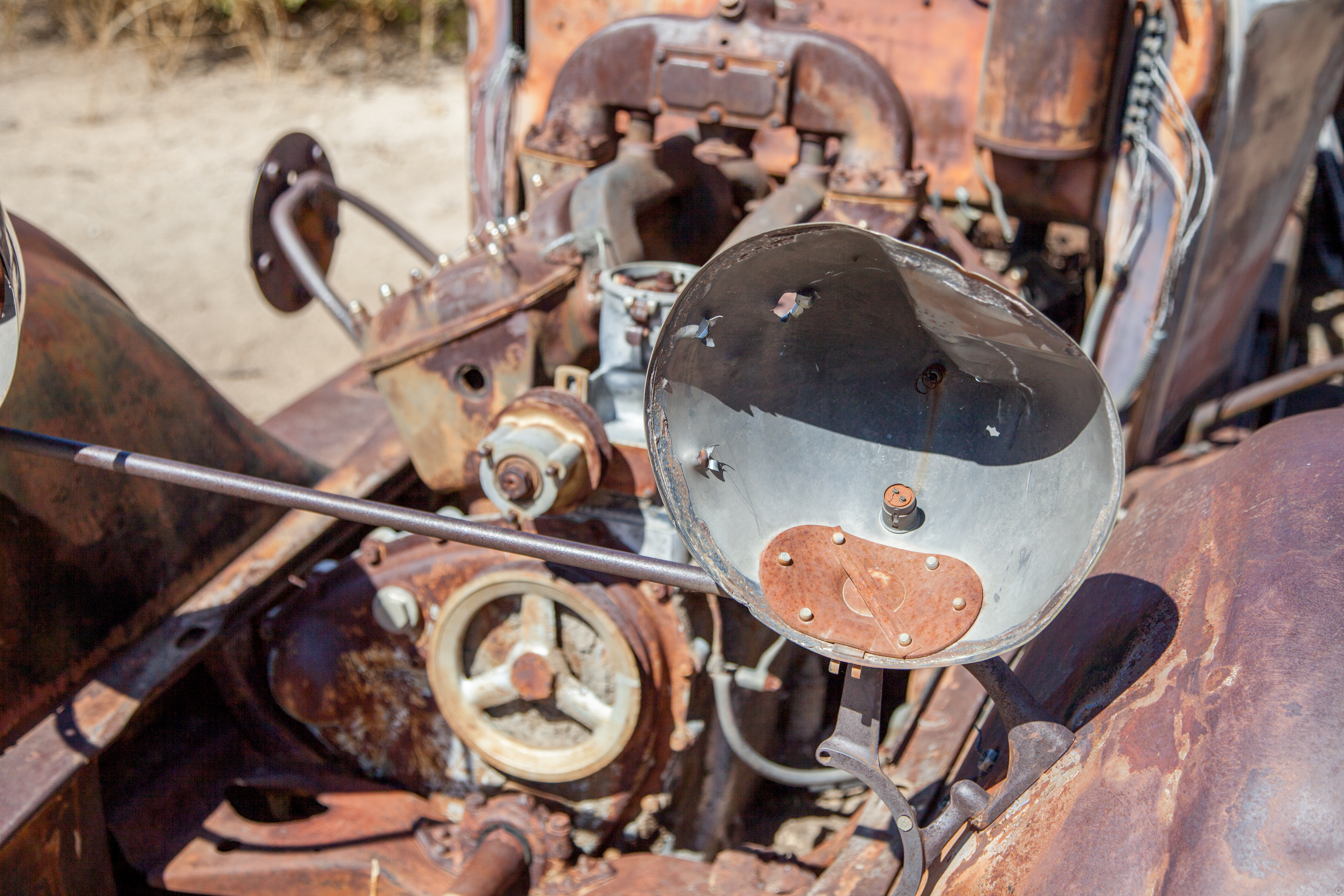 a view of a rusted out engine in the desert