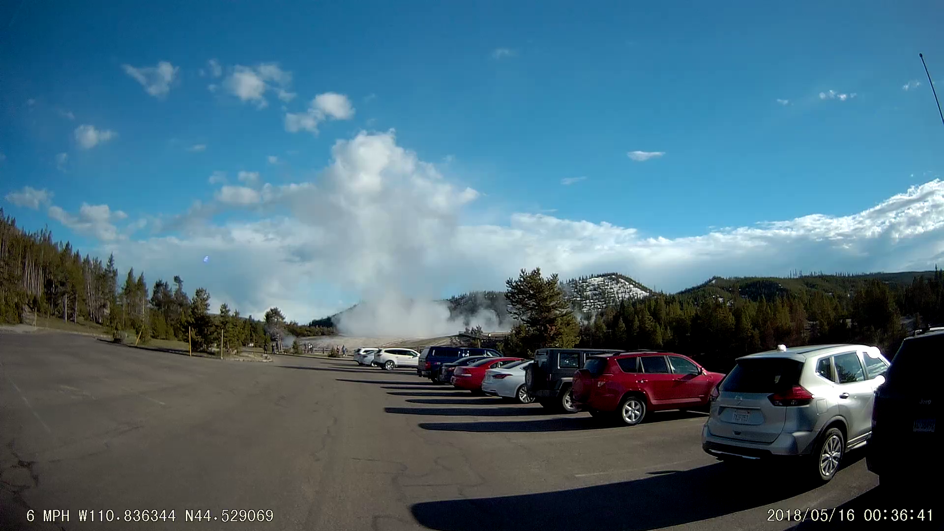 a screencap from dashcam footage showing a geyser erupting from a parking lot in Yellowstone National Park